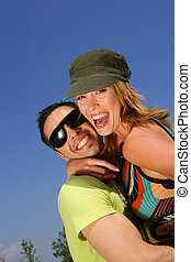 Young couple laughing against a blue sky