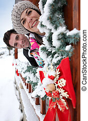 Couple leaning out of a Christmas chalet