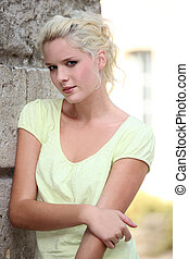Pretty young woman standing next to a stone wall