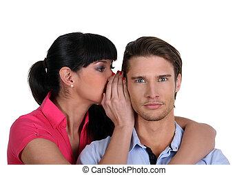 a woman whispering a secret to a man