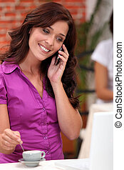 Woman on a cellphone while stirring an espresso in a...