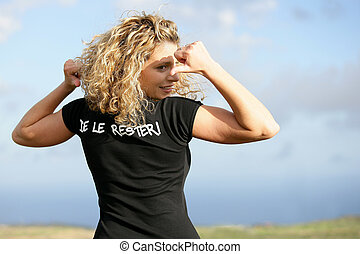 Blond woman in field pointing at t-shirt
