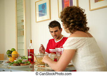 Couple eating a meal together at home
