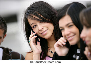 Group of youths using their mobile telephones outdoors