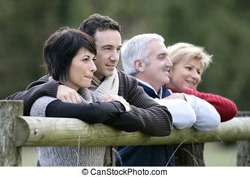 Two couples leaning on a countryside fence