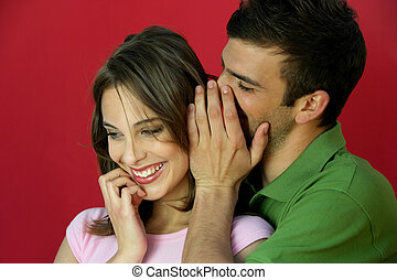 Man telling secret to woman
