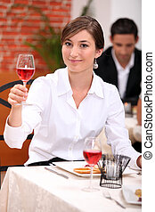 Young woman in a restaurant raising a glass of rose wine