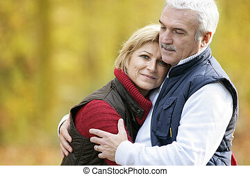 Elderly couple cuddling in park