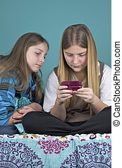 Texting Tweens - One Tween girl is texting as another looks...