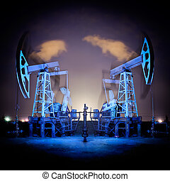 Oil Rigs at night. - Two oil pumps jack in action. Night...