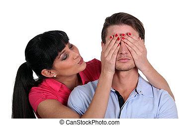 Woman covering boyfriends eyes