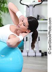 Woman doing sit-ups on gym ball