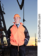 Worker in an oil field. - Worker in orange uniform and...