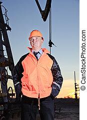 Worker in an oil field. - Worker in orange uniform and...