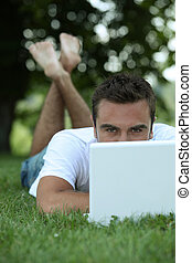 Man lying on grass in front of laptop computer