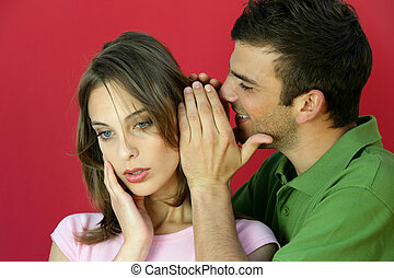 Man whispering a secret to a young woman