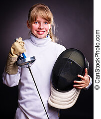 Child in fencing costume holding epee . Black background.
