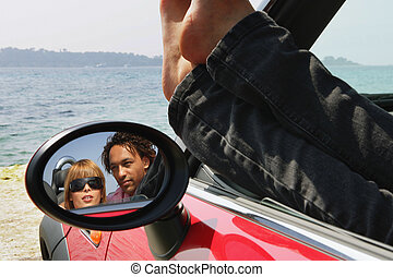 Couple sat in car at the beach