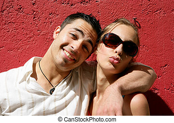 Cool couple posing against a red wall
