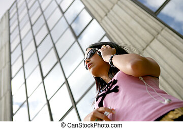Cool young woman listening to music in the city