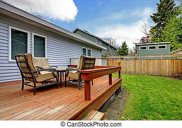 Grey small house with simple deck and outdoor chairs. -...