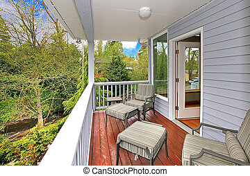 Balcony with outdoor furniture and view of woods and river....