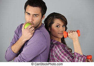 Young man with an apple and woman with a dumbbell