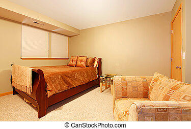 Simple basement level guest bedroom with bed and chair. -...
