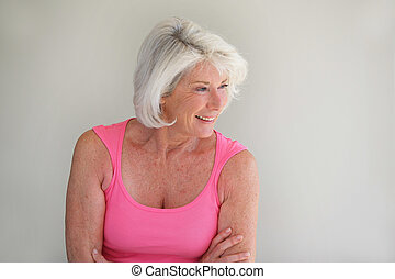 Grey-haired lady posing by wall