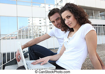 Couple sat in steps with laptop