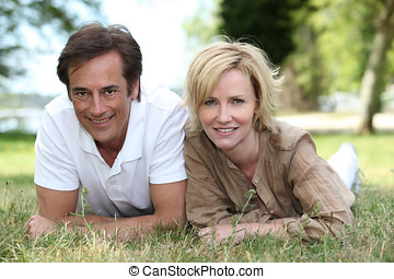 Couple lying on the grass together