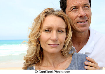 Closeup of couple on the beach, man looking to the sky