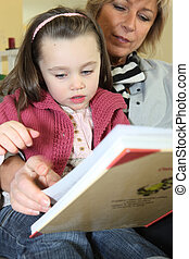 Little girl reading a book with her grandma