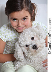 Young girl holding small white dog