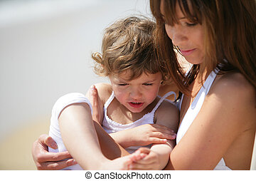 Mother holding daughter at the beach