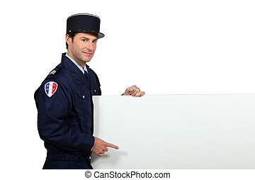 Man in a French gendarme uniform pointing at a blank board...