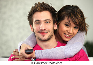 Young couple watching TV with a remote control