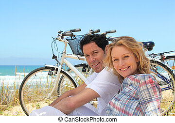 Couple on holiday sitting in front of bicycles