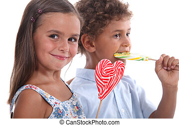 two skittish kids with lollipops