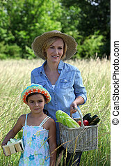 Mother and daughter carrying baskets full of vegetables