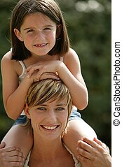 Young child riding on her mother's shoulders
