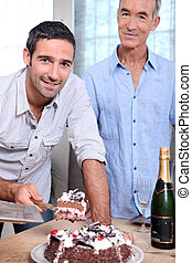 Two men cutting celebration cake