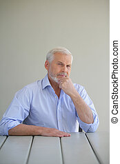 Grey-haired man stroking his beard as he thinks