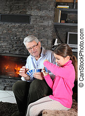 Little girl playing card game with granddad