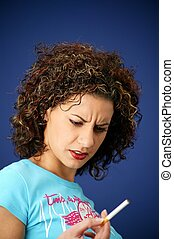 Frowning woman holding a cigarette