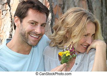 Man offering woman wild flowers