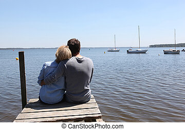 Couple sitting on the end of a pontoon