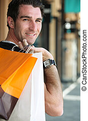 Man carrying shopping bags over shoulder