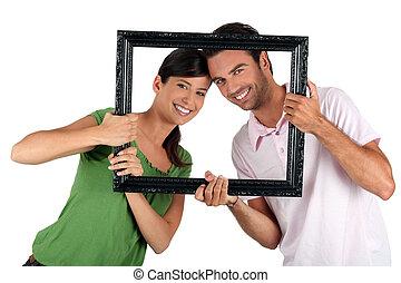 Couple holding empty art frame