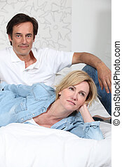 Fully clothed couple lying on a bed watching television